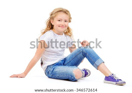 Joyful eight-year girl in casual clothes sitting on a floor and smiling. Isolated over white.