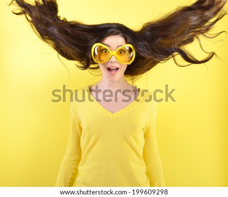 Joyful excited surprised young woman with flying hair and big funny glasses over yellow background.  - stock photo