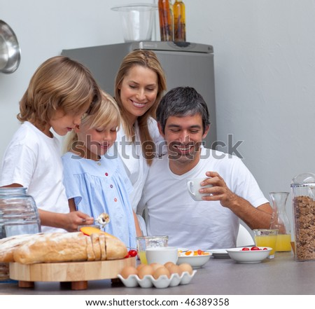 Joyful family having breakfast in the kitchen - stock photo