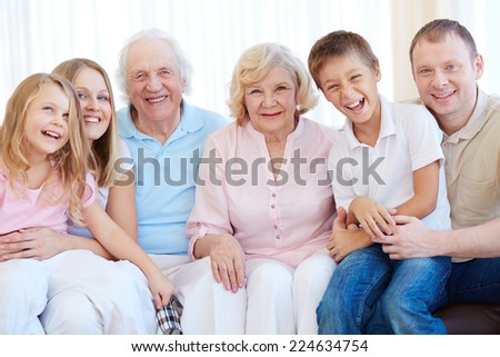 Joyful family in casual looking at camera - stock photo