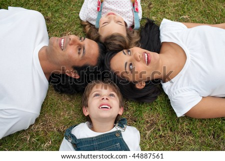 Joyful family lying in a circle on the grass in a park