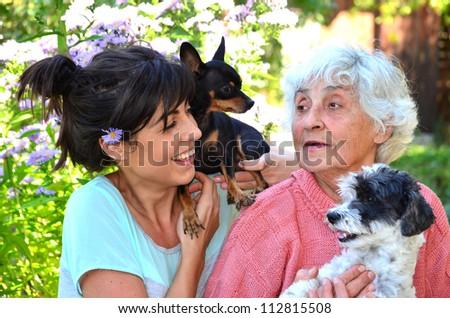 joyful family playing with black and white dog - stock photo