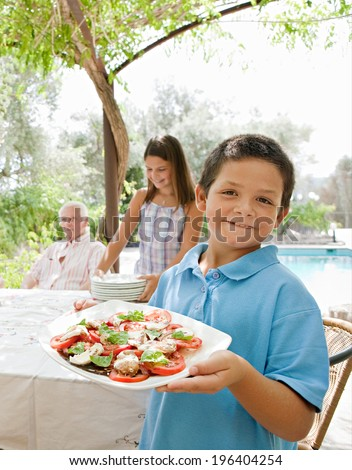 Joyful family preparing a table outdoors together, placing plates, glasses and healthy food during a sunny summer holiday day in a vacation villa home garden, outdoors. Teamwork and eating lifestyle. - stock photo