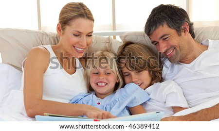 Joyful family reading a book  lying on bed