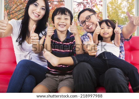 Joyful family sitting on sofa and giving thumbs up at camera with autumn background on the window - stock photo