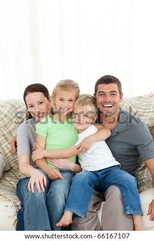 Joyful family sitting on the sofa at home - stock photo