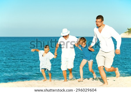 Joyful family summer sea vacation of three generations. Grandfather, son, grandson and granddaughter are running hand in hand on the beach. - stock photo