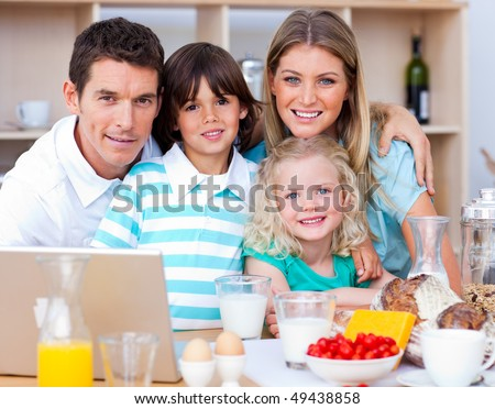 Joyful family using laptop during the breakfast in the kitchen - stock photo