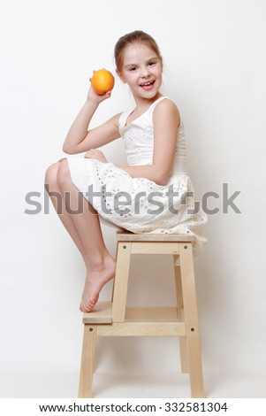 Joyful fashion little girl holding organic oranges