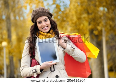 Joyful fashion woman showing digital tablet screen and holding shopping bags in autumn. - stock photo