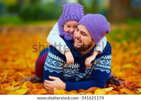 joyful father and son having fun in autumn park - stock photo