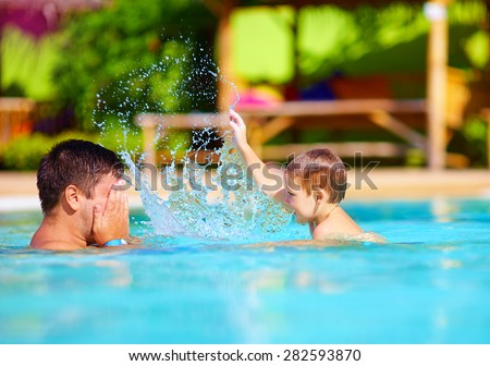 joyful father and son having fun in waterpark pool, summer holidays - stock photo