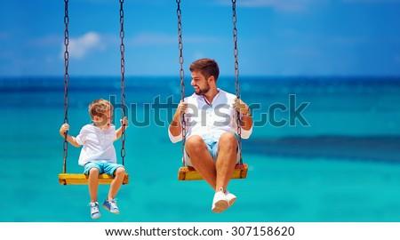 joyful father and son having fun on swings, sea background - stock photo