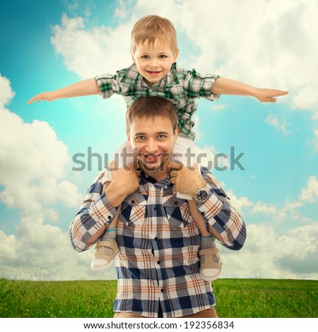Joyful father with son on shoulders carefree and happy. Fathers day, family holiday, vacation - stock photo