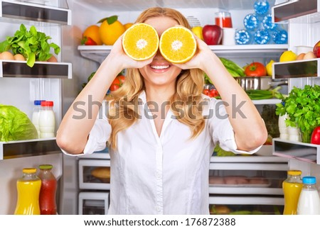Joyful female on the kitchen playing with two half of orange, tasty juicy fruit instead eyes, healthy nutrition, fun and joy concept - stock photo