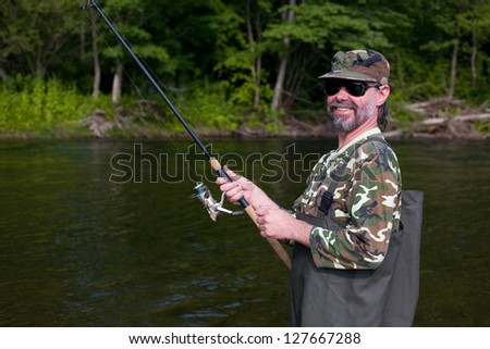 Joyful fisherman catches of salmon in the river. - stock photo
