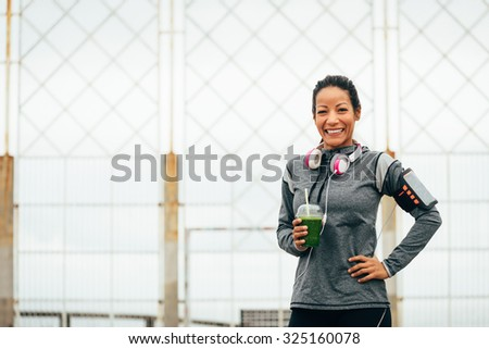 Joyful fitness woman drinking detox green smoothie during outdoor city workout rest. Sport nutrition and healthy lifestyle concept. - stock photo
