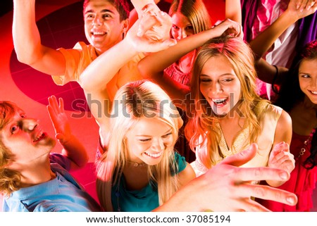 Joyful friends clubbing at discotheque next to each other with smiles - stock photo