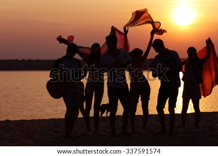 Joyful friends having fun on the shore at sunset outdoors - stock photo