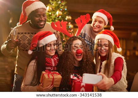 Joyful friends making selfie on Christmas evening - stock photo