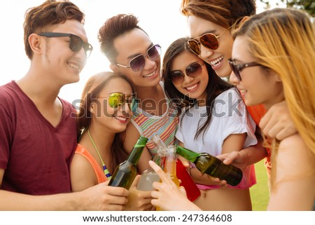 Joyful friends toasting with beer bottles - stock photo