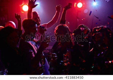 Joyful friends with champagne dancing in disco club - stock photo