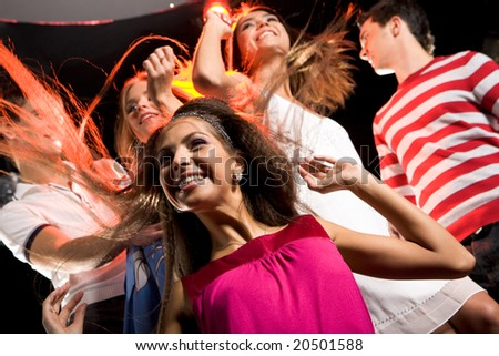 Joyful girl having fun in club on background of her danscing friends