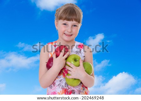 joyful girl holding a lot of apples.healthy food concept,active lifestyle,happiness concept,carefree childhood concept. - stock photo