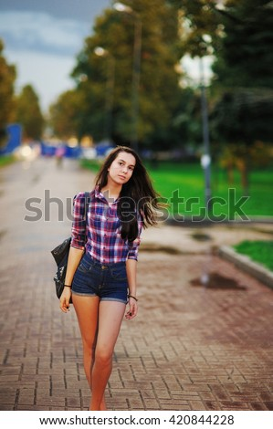 joyful girl in a plaid shirt and denim shorts walking on the street after the rain. Her hair is wet. - stock photo