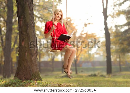 Joyful girl in a red dress reading a book seated on swing in a park  - stock photo