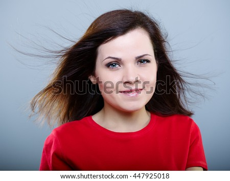 Joyful girl in a red shirt with hair flying on a gray background - stock photo