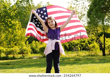 joyful girl in a white dress holding a large American flag