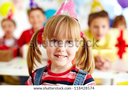 Joyful girl in birthday cap looking at camera with her friends on background - stock photo