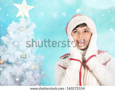 Joyful girl in Santa cap expressing amazement with decorated firtree behind