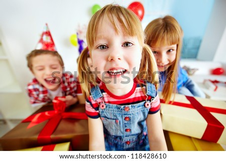 Joyful girl looking at camera with her happy friends on background - stock photo