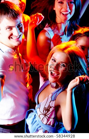 Joyful girl raising her arms during dance with friends near by - stock photo