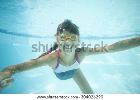Joyful girl swimming underwater in pool - stock photo