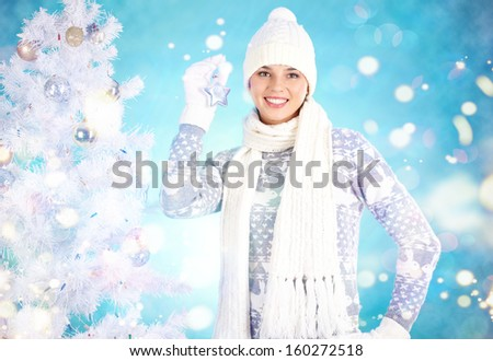 Joyful girl with decorative toy star looking at camera with xmas tree near by