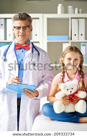 Joyful girl with teddy bear and her doctor looking at camera in hospital - stock photo