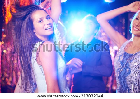 Joyful girls and guys dancing in night club - stock photo