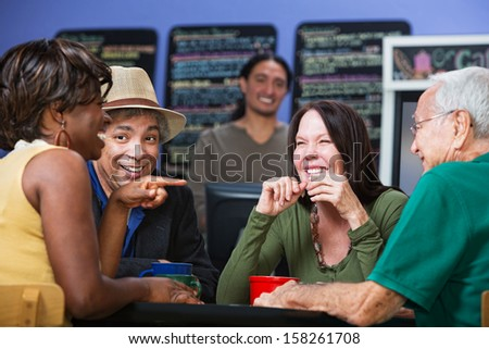 Joyful group of adults sitting in a cafe - stock photo