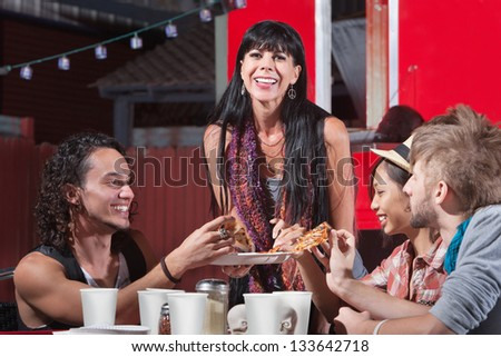 Joyful group of friends sharing pizza slices outdoors