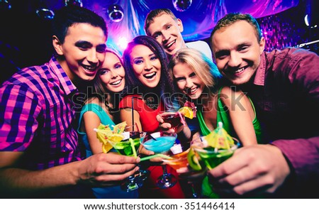 Joyful group of friends toasting with cocktails at party - stock photo