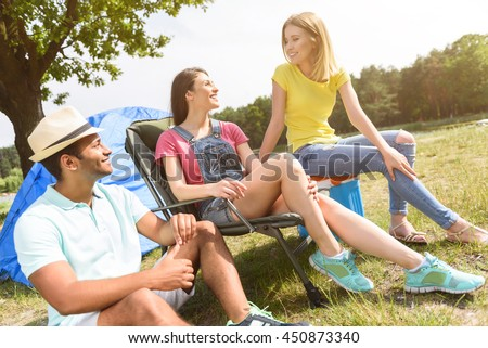 Joyful guy and girls resting in forest