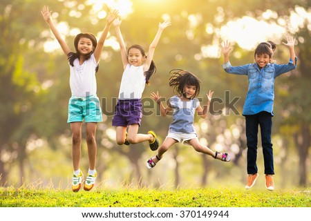 Joyful happy asian family jumping together at outdoor park - stock photo