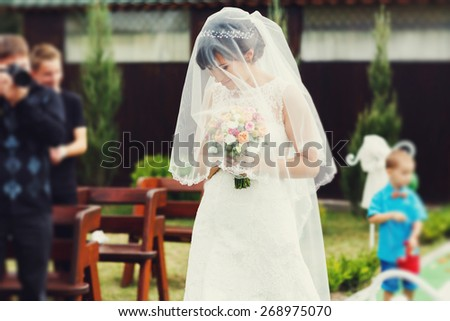 joyful happy bride in a white dress with lace with a bouquet of flowers at a wedding ceremony - stock photo