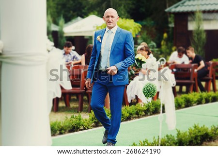 joyful happy bride in blue suit is on the green track at wedding ceremony - stock photo