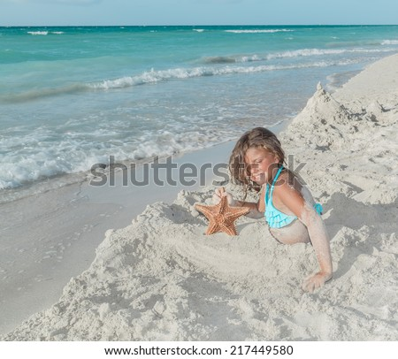 joyful, happy, smiling little girl sitting on white sand beach near the ocean and holding starfish