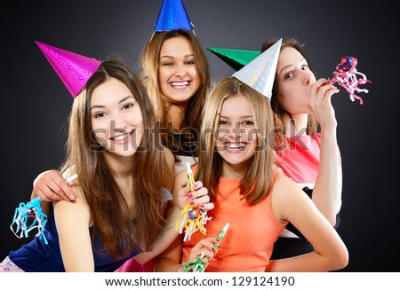 Joyful happy smiling teen girls have fun on birthday party, over black