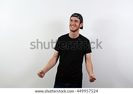 Joyful Happy Smiling Young Adult Male in Dark T-Shirt and Baseball Hat Worn Backwards - stock photo